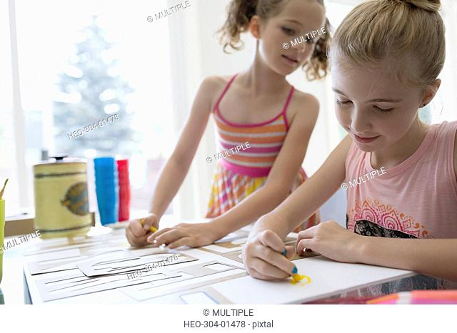 Girls coloring and using stencils at dining table
