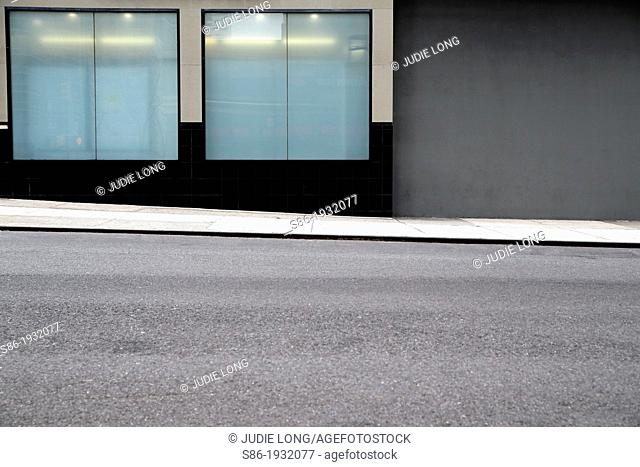 Two Frosted Glass Display Windows Next to a Gray Painted Cement Wall