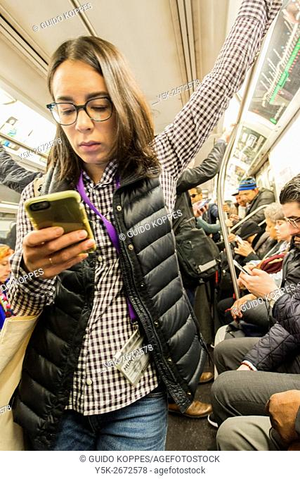 New York City, USA. Female commuter hanging around the subway train, while playing with her smartphone