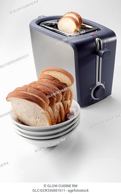 Close-up of white breads in a bowl with a toaster