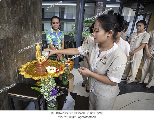 The staff of the Hotel Botanica of Khao Yai doing the honors to Buddha at the beginning of the day to celebrate the Sogkran. Thai New Year
