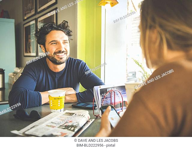 Hispanic couple talking in coffee shop