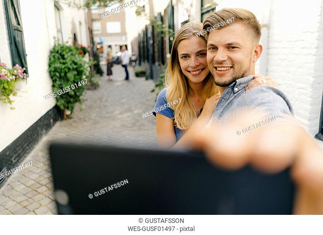 Netherlands, Maastricht, happy young couple taking a selfie in the city