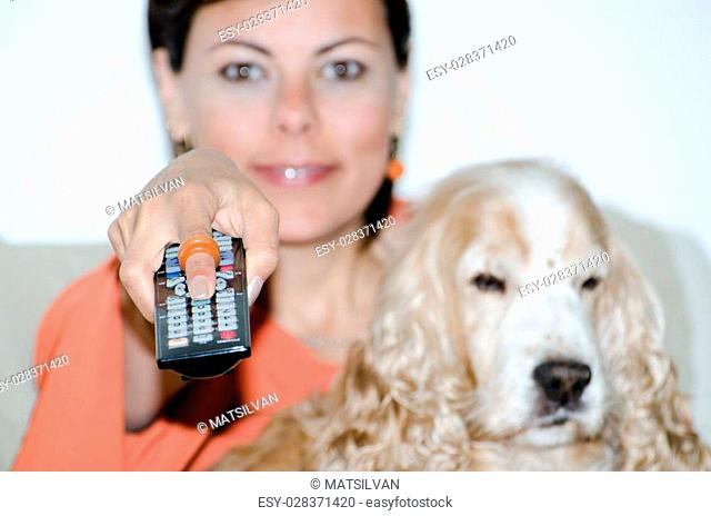Woman with a remote control and a cocker spaniel dog