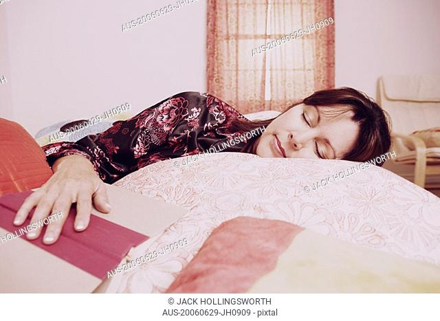 Mature woman sleeping on the bed with her hand on an open book