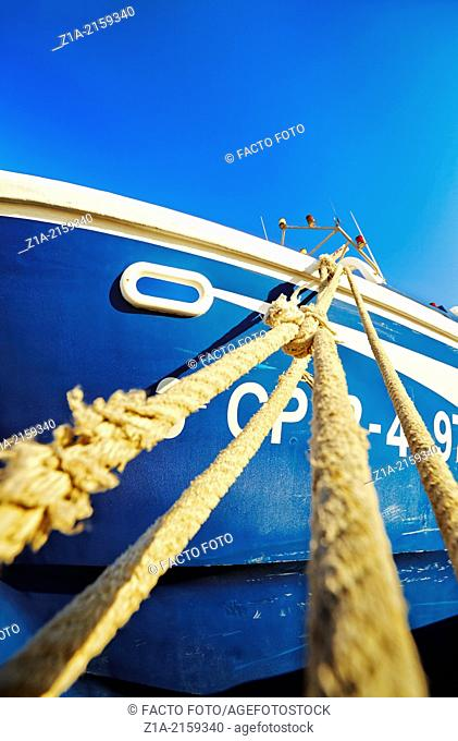 Tied ropes of a blue boat at the harbour. Denia. Alicante. Spain