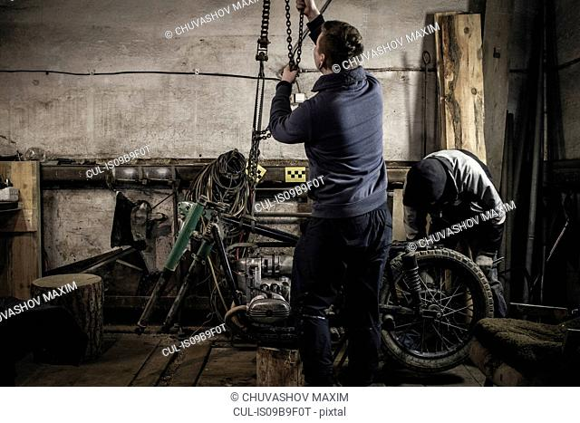 Mechanic hoisting dismantled vintage motorcycle in workshop