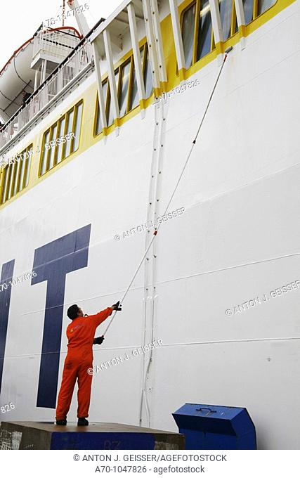 Painting a Comarit ferry boat in the port of Tangier, Morocco