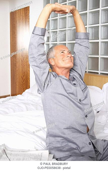 Man stretching on bed in modern home