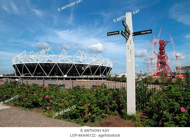 England, London, Stratford. The London 2012 Olympic stadium, the ArcelorMittal Orbit observation tower and signpost in the Olympic Park
