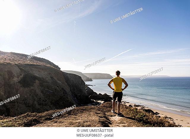 France, Crozon peninsula, sportive young man at steep coast looking at view