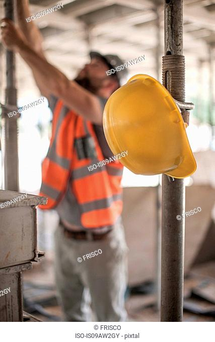 Male builder working on scaffolding on construction site