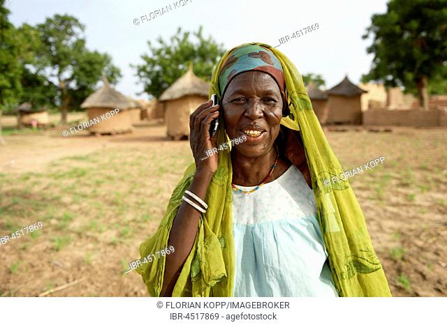 Woman with mobile phone in traditional village, Toeghin village, Oubritenga province, Plateau Central region, Burkina Faso