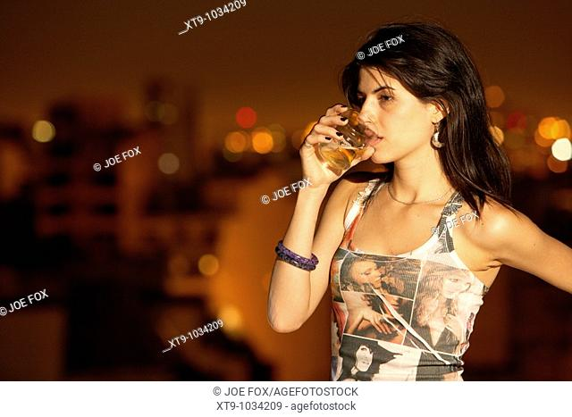 young hispanic latin woman drinking glass of beer looking sad in buenos aires argentina