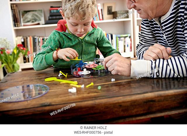 Grandfather and grandson assembling toy clock