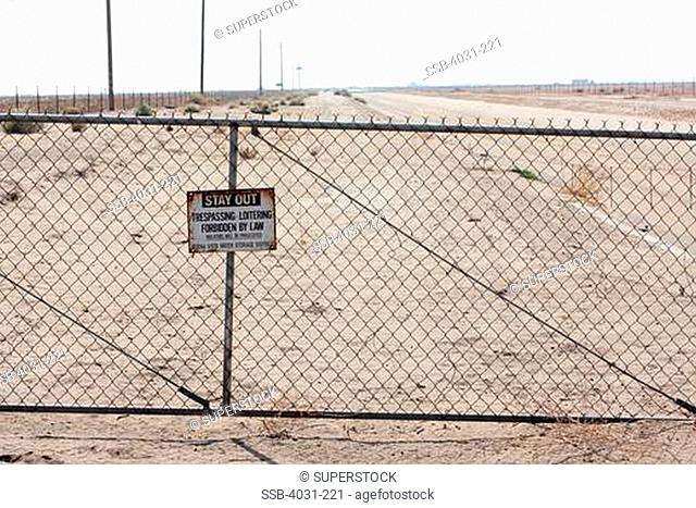 USA, California, Kern county, No Trespassing sign on gate to empty irrigation canal