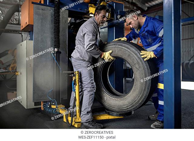 Two tire repairmen lifting tire in factory