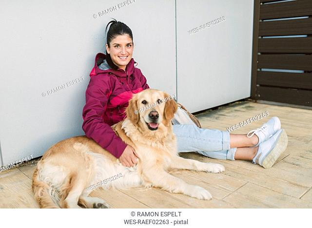 Portrait of a smiling young woman with her Golden retriever dog sitting at a wall