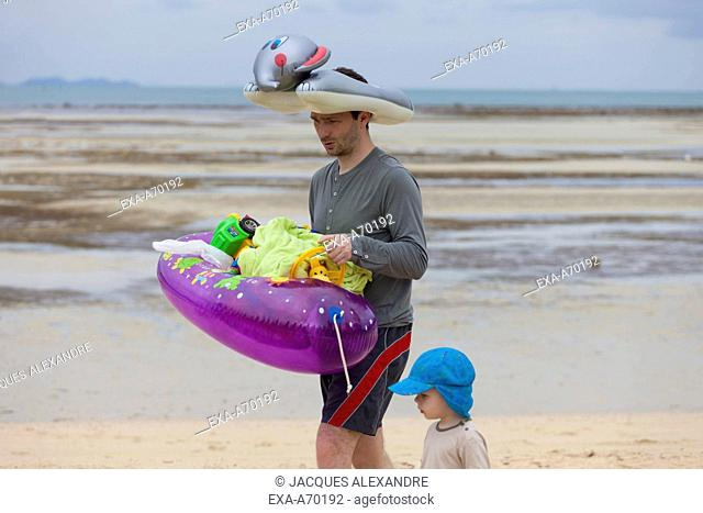 father and child walking at beach