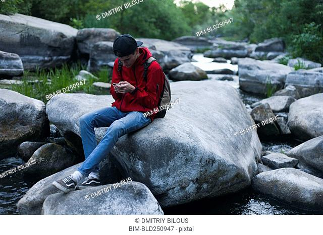 Caucasian man sitting on rock in river texting on cell phone