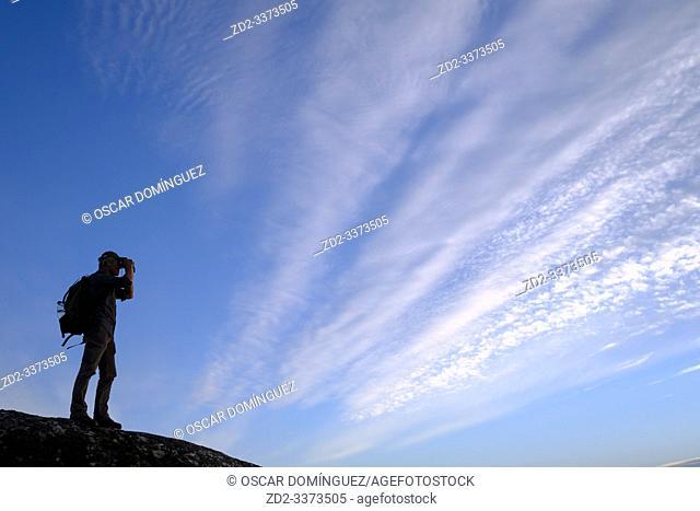 Birdwatcher silhouetted against clouds. Taejo International Park. Extremadura. Spain