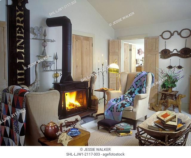 LIVING ROOM - wood burning stove in country home 19th century weather vanes, quilt, and old optician sign, beige wing chairs with quilts, books, floor lamp