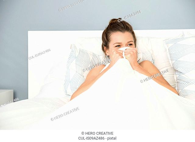 Young woman sitting up in bed hiding