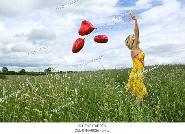 Woman walking with balloons in field