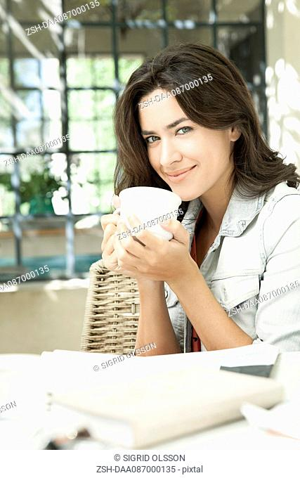 Young woman enjoying cup of coffee outdoors