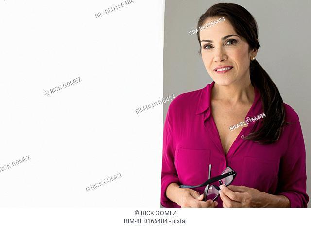 Smiling Hispanic woman holding eyeglasses