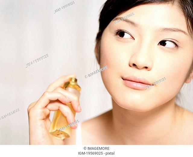 Young woman spraying the perfume