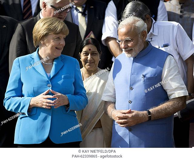 German chancellor Angela Merkel and Indian Prime Minister Narendra Modi pose on the red carpet on the stairs to the Hyderabad House for a group picture after...