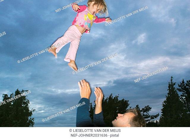 Man throwing girl into air