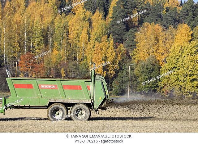 Salo, Finland - October 14, 2018: Bergmann manure spreader pulled by tractor at work on stubble field on a beautiful day of autumn