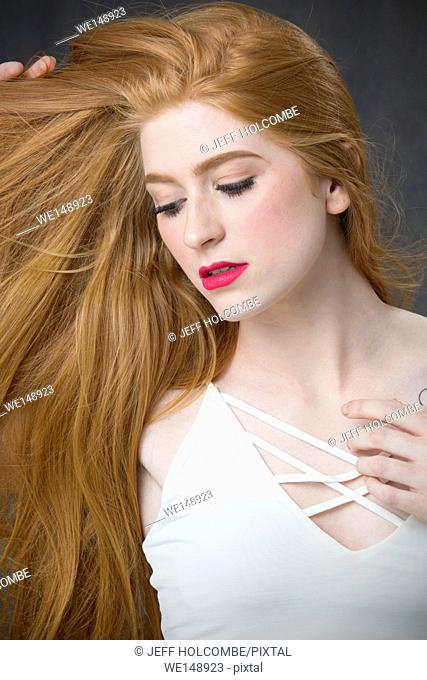 Head and shoulders portrait of beautiful young woman with bountiful red hair, looking aside