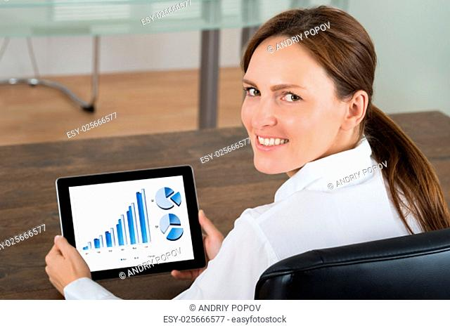Young Businesswoman With Digital Tablet Showing Graphs On Display In Office