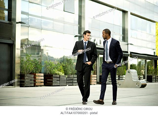Business colleagues walking and talking together