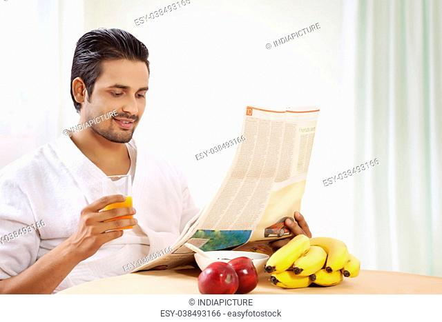 Portrait of man reading newspaper at breakfast table