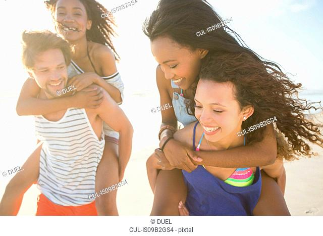 Young man and woman piggybacking friends on beach, Cape Town, South Africa