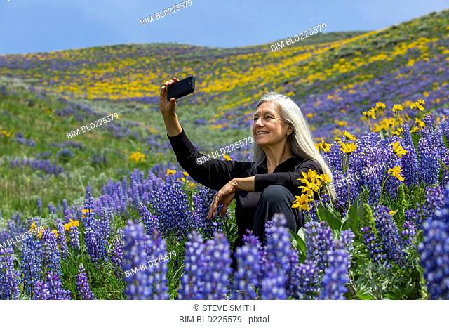 Caucasian woman posing for cell phone selfie hillside with wildflowers
