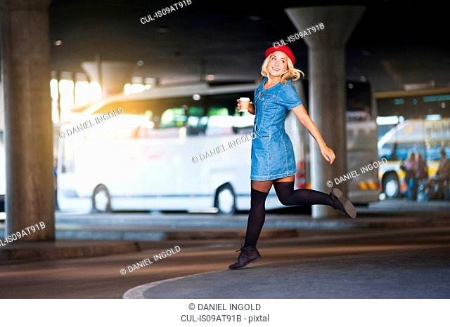 Young woman wearing red hat running in bus station