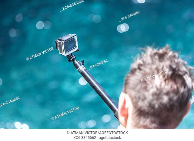 boy recording images with a Go-pro camera mounted on a stick above tjhe sea