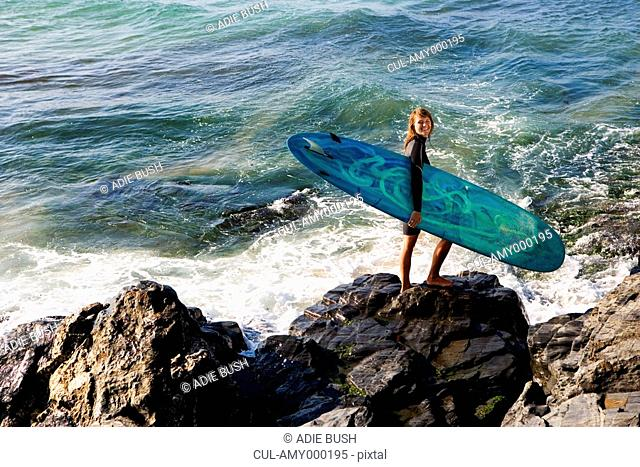 Woman standing on large rocks with a surfboard smiling