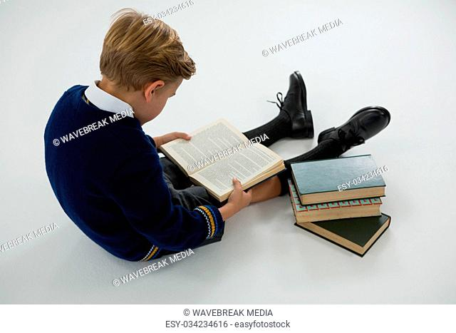 Schoolboy reading book on white background