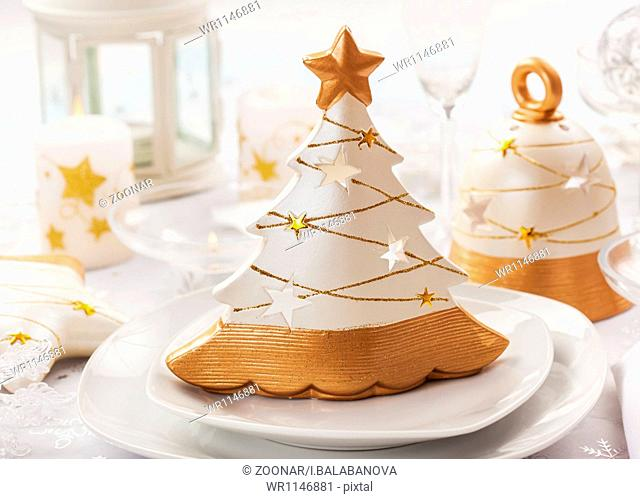 Festive table for Christmas with small tree in white and golden tones