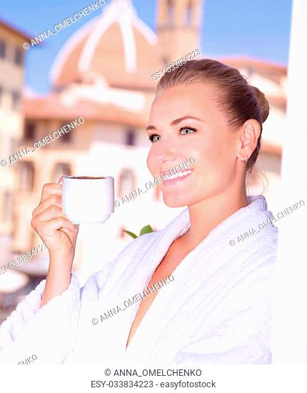 Portrait of beautiful happy woman drinking coffee in hotel room in Florence, Italy, Europe, standing on balcony on wonderful cityscape background