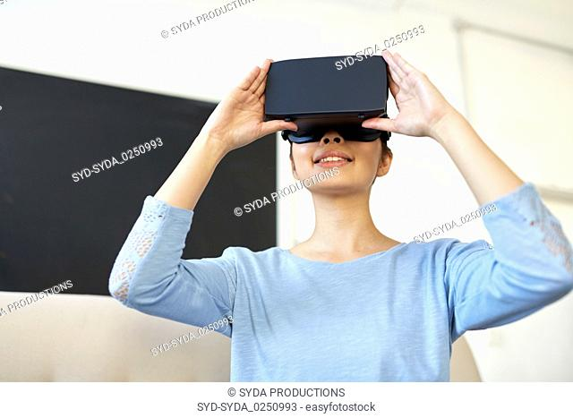 happy woman with virtual reality headset at office