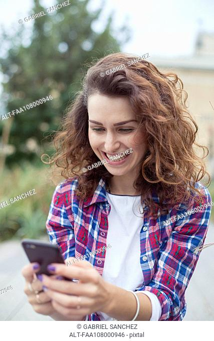Cheerful young woman using smartphone outdoors