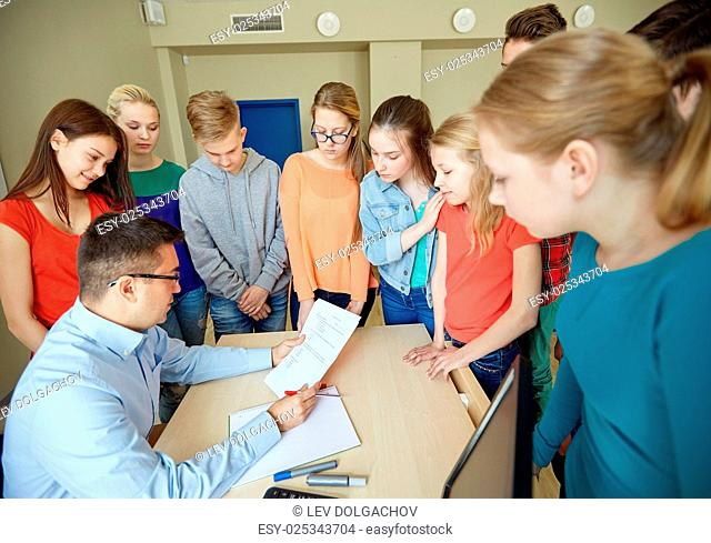 education, school, learning, teaching and people concept - group of students and teacher with tests in classroom