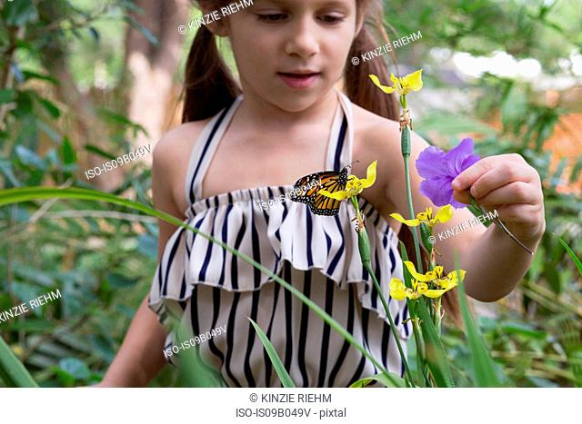 Girl looking at monarch butterfly on flower